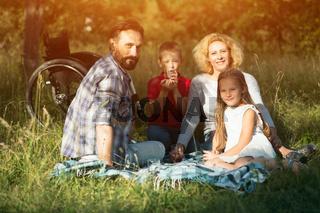 Happy family making family portrait in park. Paraplegic