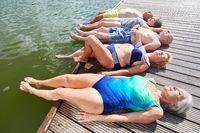 Senioren entspannen auf Steg am Badesee