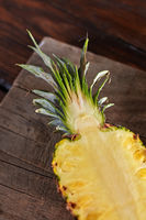 Juicy half of pineapple with green leaves on a wooden board on the kitchen table. Vitamin Fruit. Top view