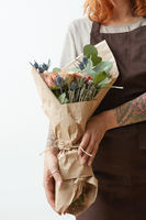 Female in a brown apron with red hair hold nice bouquet from living coral colored roses and eryngium on a light