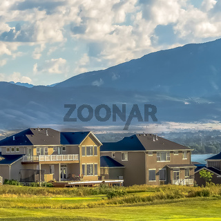 Square frame Expansive grassy terrain in front of homes under cloudy blue sky on a sunny day