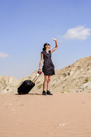 Woman in the desert with her luggage