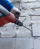 construction worker using a handheld demolition hammer and wall breaker to chip away and remove old floor tiles during renovation work