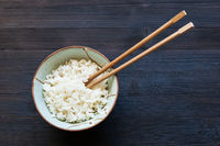 chopsticks in bowl with boiled rice on dark
