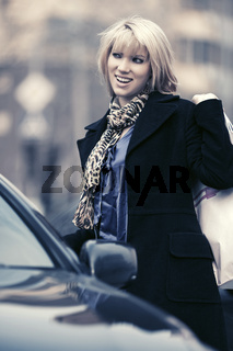 Happy young fashion woman with shopping bags next to her car
