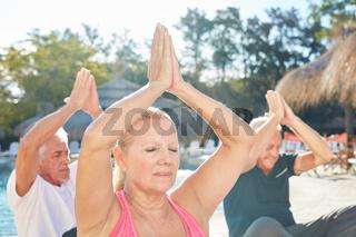 Senioren sitzen und meditieren am Pool