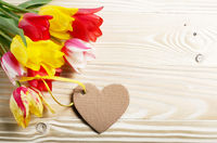 Colorful tulip flowers and heart shape cards on wooden table background with space for text