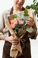 Smilling girl florist with creative bouquet from fresh flowers roses in a paper on a light background. Close-up. Congratulation card.