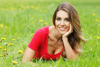 young woman in red dress lying on grass young woman in red dress lying on grass