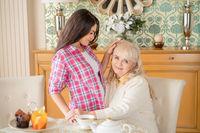 Cheerful daughter hugs her elderly mother