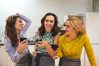 Cheerful friends preparing a meal together and drinking red wine in the kitchen