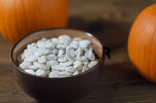 Pumpkins and seeds in bowl on wood
