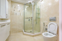 Bright bathroom interior with glass shower and toilet