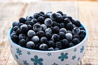 White bowl full with frozen aronia berries