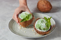 Womans hands take a half of coconut with homemade green ice cream from plate on a gray concrete.