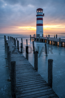 Winter landscape with lighthouse on a lake at sunset