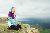 A girl-traveler with multicolored hair sits on the edge of a cliff and looks to the horizon on a background of a rocky plateau