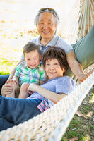 Chinese Grandparents In Hammock with Mixed Race Child