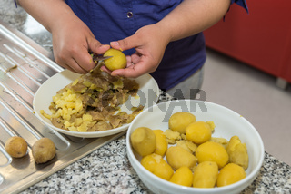 Köchin schält in der Küche frisch gekochte Kartoffeln - Nahaufnahme