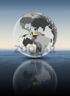Colombia on translucent globe above water