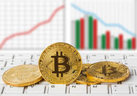 Bitcoins on computer and diagram - business background
