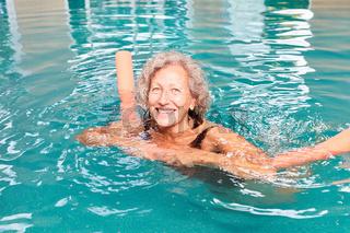 Frau lernt Schwimmen mit Schwimmnudel