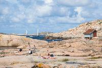 Sunbathing people on rocks by the sea