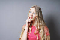 pensive young woman with hand on chin