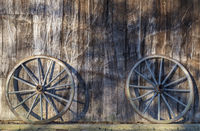 Zwei Wagenräder lehnen an einer Scheunenwand