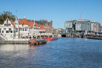 Amsterdam canals with launches and buildings near central railway station