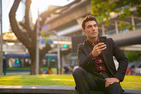 Young thoughtful Hispanic businessman holding phone and sitting with nature in city