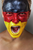 Emotional football fan with German flag painted on his face over gray background