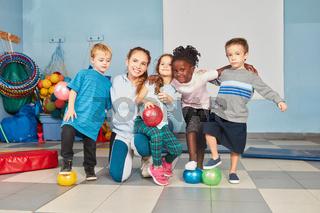 Lehrerin und Kinder Gruppe mit Bällen