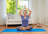 woman meditating in lotus pose at home
