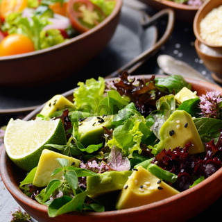 Clay dish with salad of avocado, green and violet lettuce, lamb's lettuce and oregano flowers on slate stone tray with soy sauce lime and sesame aside