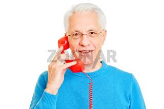 Senior Mann telefoniert mit altem Telefon