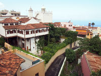 panoramic  view of La Orotava in Tenefife showing colorful painted buildings profuse plants and the sea