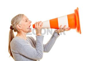 Ältere Frau schreit in Pylon als Megafon