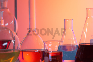 Backlit laboratory test flask containing colorful liquids.
