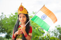 Maski, India August 15, 2019 : Small cute little Indian Girl kid in Bharat mata or Mother India attire with Indian Flag in hand.
