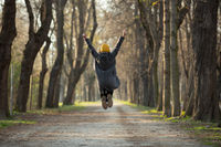 Excited young woman is jumping with arms raised up