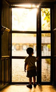 Backlit toddler standing in front of door