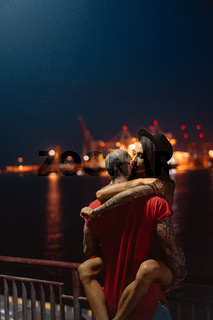 Guy and girl hugging each other on a background of the night port