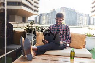 Student mit Laptop entspannt sich am Feierabend