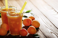 Apricot smoothie in mason jar on wooden table