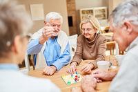 Rentner Paar spielt mit Freunden Brettspiel