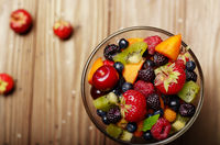 Top view of assorted fruits in glass bowl on kitchen wooden table