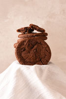 Chocolate Chocolate Chip cookies on a pedestal covered with a kitchen towel