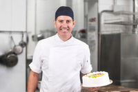 Smiling pastry Chef showing a cake