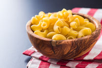 Uncooked elbow macaroni in bowl.